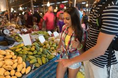 Touristes sur les fruits frais de achat exotiques tropicaux des jeunes du marché dans le bazar traditionnel asiatique Images stock