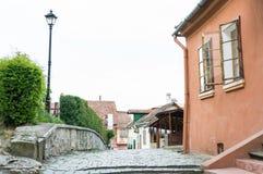 Touristes sur les rues de la ville médiévale de Sighisoara, Roumanie Bâtiments et cafés antiques de rue images libres de droits