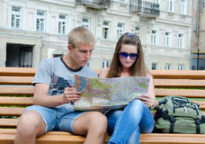 Touristes sur un banc regardant une carte Photo libre de droits