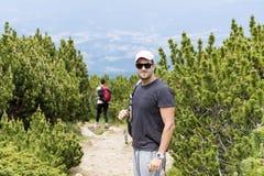 Touristes trimardant dans une haute montagne, dans une forêt de pin Image stock