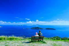 Touristes, un homme et une femme s'asseyant sur un banc, admirant gagné Photographie stock libre de droits