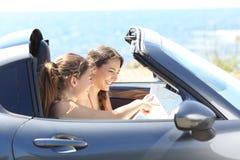Touristes vérifiant le guide à l'intérieur d'une voiture des vacances image libre de droits
