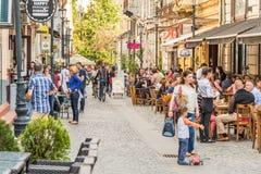 Touristes visitant et prenant le déjeuner au café extérieur de restaurant Image stock