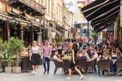 Touristes visitant et prenant le déjeuner au café extérieur de restaurant Images stock
