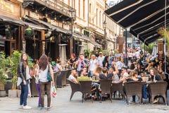Touristes visitant et prenant le déjeuner au café extérieur de restaurant Photographie stock
