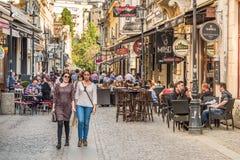 Touristes visitant et prenant le déjeuner au café extérieur de restaurant Photographie stock libre de droits