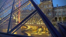 Touristes visitant le Musée d'Art de Louvre, vue par la pyramide en verre, visite vers Paris banque de vidéos