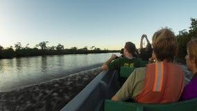 Touristes voyageant en canoë sur une rivière en Amazone tout en prenant des photos de coucher du soleil image stock