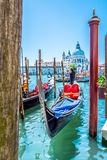 Touristic attractions in Venice - gondola and basilica. View at gondola dock station and church Santa Maria di Salute in background, unique touristic city Stock Photography