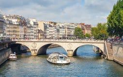 Touristic boat by Batobus goes under the Pont Neuf Stock Photo