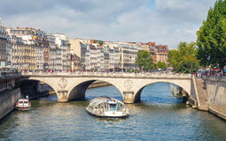 Touristic boat by Batobus goes under the Pont Neuf Stock Photo