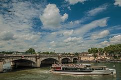 Touristic boat and bridge over the Seine River under a sunny blue sky in Paris. Royalty Free Stock Photos