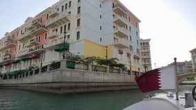 Venice Doha boat. Touristic boat with flag of Qatar on Venetian canals of picturesque Qanat Quartier icon of Doha, Venice at the Pearl, Persian Gulf, Middle East stock video