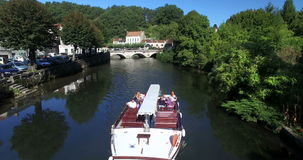 Touristic boat floats on the river in Brantome. BRANTOME, FRANCE - 17 SEPTEMBER 2013: Aerial view of touristic boat floats on the river in Brantome. Brantome is stock video footage