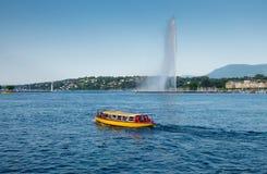 Touristic boat at Geneva Lake on Jet d\'Eau fountain background. Sunset time. Switzerland royalty free stock photos