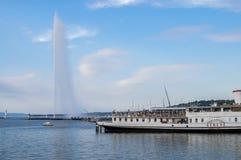 Touristic boat at Geneva Lake on Jet d\'Eau fountain background. Sunset time. Switzerland. GENEVA, SWITZERLAND - JUNE 24, 2017: Touristic boat at Geneva Lake on royalty free stock photos