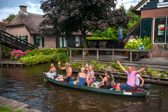 Touristic boat  in Giethoorn with joyfull tourists on excursion. Giethoorn, The Netherlands, Circa July 2013 Stock Image