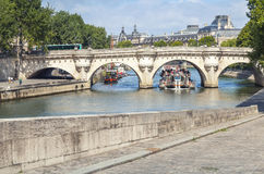 Touristic boat goes under the Pont Neuf, Paris Stock Photo