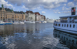 Touristic boat/hotel buildings, Stockholm. A view of the harbor of Stockholm with some touristic boats and sun light lit building behind; there are blue skies Stock Photo