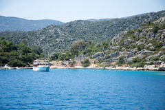 Touristic boat near shores of sunken city of Kekova in Uchagiz b. KEKOVA, TURKEY - MAY 21 : touristic boat near unken city of Kekova close to rocks in 2016 Royalty Free Stock Photo