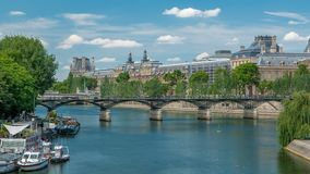 Touristic boat passes below Pont des Arts, on boat station on Seine river timelapse in Paris.