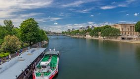 Touristic boat passes below Pont des Arts and stop on boat station on Seine river timelapse hyperlapse in Paris. Paris is the top touristic destination in stock footage