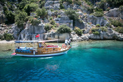 Touristic boat passing by sunken city of Kekova. KEKOVA, TURKEY - MAY 21 : touristic boat passing by sunken city of Kekova under turkish flag close to rocks in Stock Photo