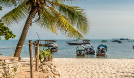 Touristic boats anchored near sandy beach, Zanzibar Stock Image