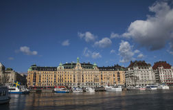 Touristic boats and hotel buildings, Stockholm. A view of the harbor of Stockholm with some touristic boats and sun light lit building behind; there are blue royalty free stock photography