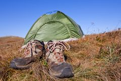 Touristic boots near a tent Royalty Free Stock Image