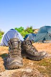 Touristic boots near a touristic tent Stock Photos