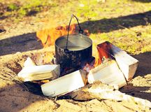 Touristic Bowler. Sooty cauldron on campfire at forest, sunny day Royalty Free Stock Photos