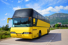 Touristic bus on the parking. Empty touristic bus is standing on the parking near the mountain Stock Photos