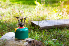 Touristic camping gas burner. Touristic camping burner installed on gas cylinder tank in background of summer forest. Compact kitchen stove for cooking hot food Stock Image