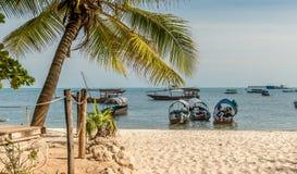 Touristic fartyg ankrade nära den sandiga stranden, Zanzibar Fotografering för Bildbyråer