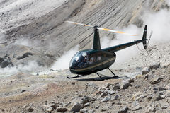 Touristic Helicopter in crater of active volcano Stock Photo