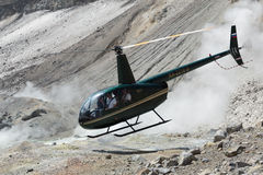 Touristic helicopter takes off in crater of active volcano Royalty Free Stock Image