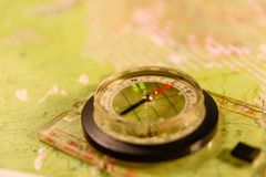 Magnetic compass lying on topographical map royalty free stock image