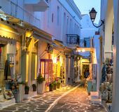 Touristic narrow street with souvenirs shops in the evening Stock Photos