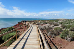 Touristic path in Punta Tomba coastal penguin park. Cape with red cliffs in the dark blue waters of the ocean. Atlantic coast of Argentina, Touristic path in Royalty Free Stock Photos