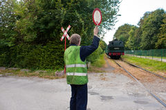 Touristic railway flagman at level crossing stopping car traffic Royalty Free Stock Images