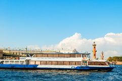 Touristic sailboat floating on Neva river and rostral columns and old stock exchange building in St Petersburg, Russia Royalty Free Stock Photo