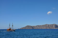 Touristic ship and The famous Red beach in Santorini island, Greece. Touristic ship in mediterranean sea near terracotta rock and blue sky background. The Royalty Free Stock Image