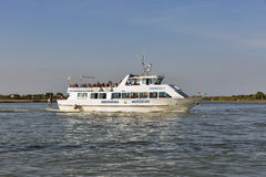 Touristic ship sails in Venetian lagoon close to Burano, Italy Royalty Free Stock Image
