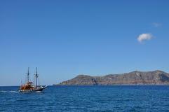 Touristic skepp och den berömda röda stranden i den Santorini ön, Grekland Royaltyfri Bild