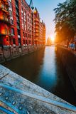 Touristic spot old red brick illuminated buildings, canal and square in golden sunset light. Speicherstadt Hamburg Stock Photography