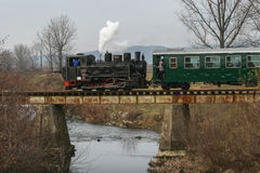 Touristic steam engine train. Brad, Romania, December12, 2009: An old steamed cog train is crossing a bridge in Brad, on winter holydays Royalty Free Stock Images