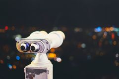 Touristic telescope look at city with view of Barcelona Spain, close up old metal binoculars on background viewpoint, hipster coin stock image