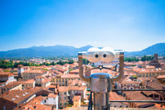 Touristic telescope look at the small italian city. Close up metal binoculars on background viewpoint overlooking the Royalty Free Stock Image