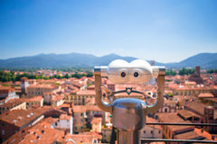 Touristic telescope look at the small italian city. Close up metal binoculars on background viewpoint overlooking the Royalty Free Stock Photos